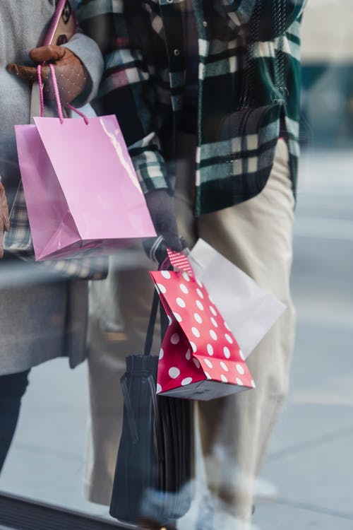 Unrecognizable female friends in outerwear standing on sidewalk near showcase with purchases in bags on street in city on blurred background