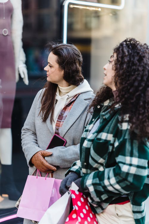 Pensive women friends in casual clothes standing with shopping bags near shop on street in daytime