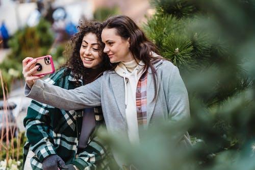 Cheerful friends taking selfie on smartphone on street