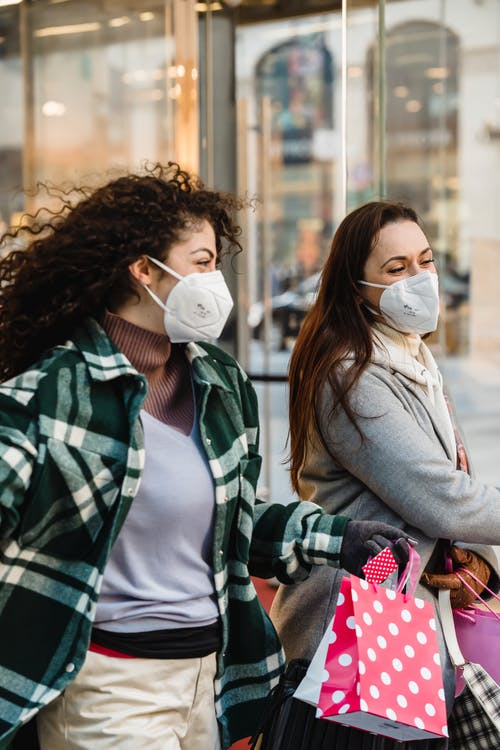 Cheerful women friends in protective masks and trendy outfits with shopping bags walking on street in city during pandemic