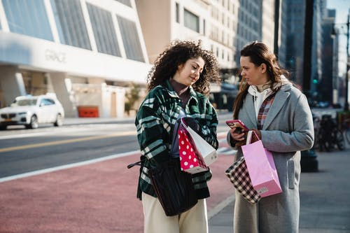 Friends standing with colorful shopping bags on street in sunny day