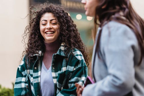 Cheerful ethnic woman with long curly hair walking with friend on city street in daylight