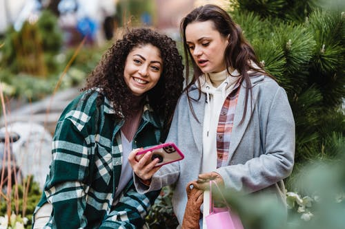 Cheerful ethnic woman with curly hair in trendy clothes smiling and looking away while standing with pensive friend browsing mobile phone on street against green plants in daylight