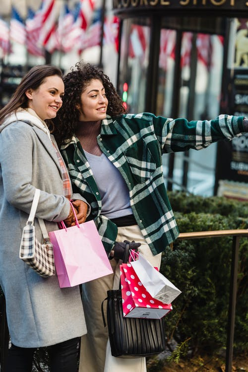 Positive young ethnic lady in casual clothes standing on city street with female friend and pointing away after shopping