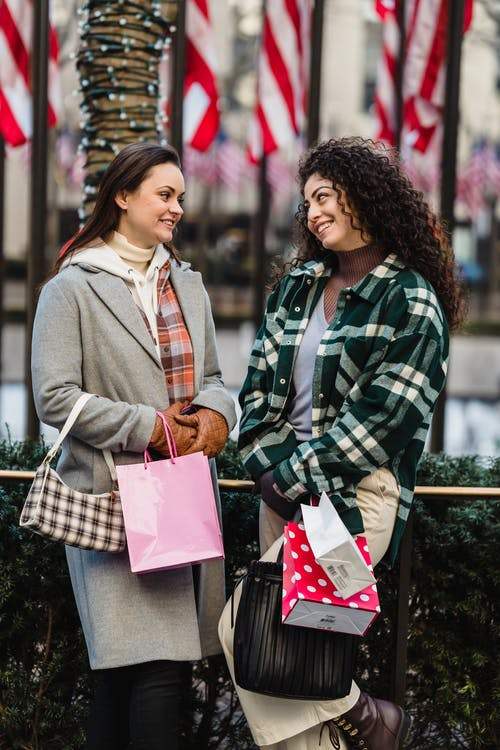 Smiling young diverse female millennials chilling on street after shopping