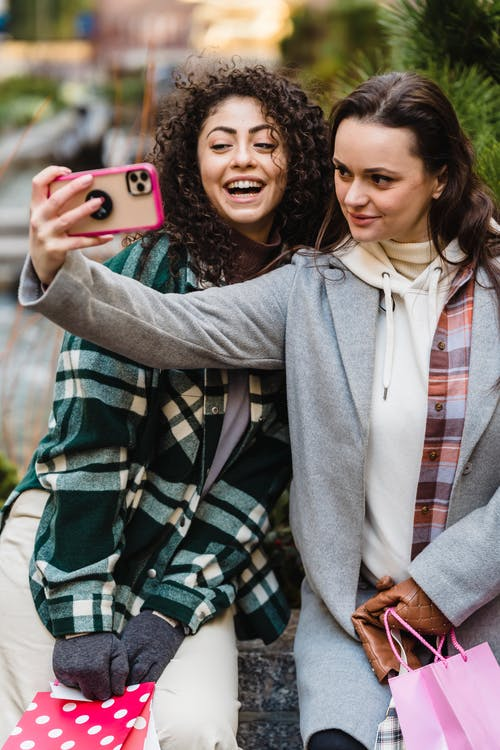 Happy young multiethnic female friends taking selfie in city after shopping