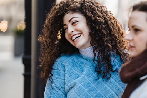 Cheerful young ethnic lady with long curly hair in warm sweater laughing an looking away while spending time on city street with female friend