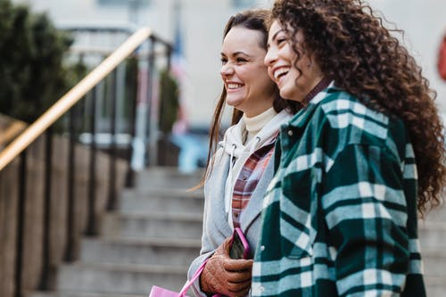 Side view of joyful young multiethnic female best friends with dark hair in stylish outfits smiling happily looking away while standing on city street near staircase in daytime