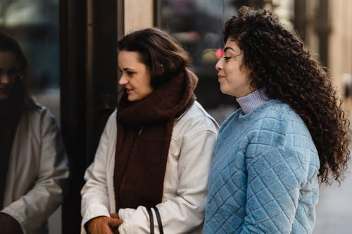 Side view of trendy young multiracial females in stylish warm clothes standing near glass showcase of fashion boutique before shopping