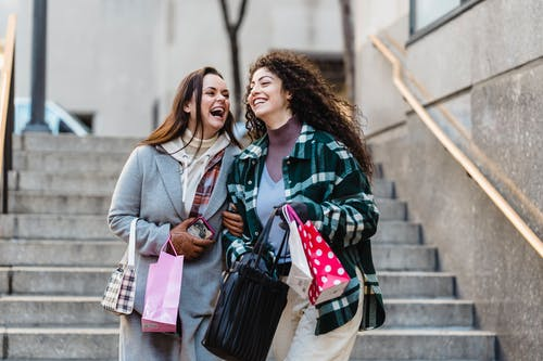 Joyful young stylish multiracial female best friends in trendy warm clothes laughing while walking downstairs with shopping bands in hands on city street