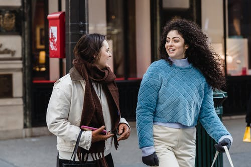 Happy stylish diverse female friends communicating while strolling on street