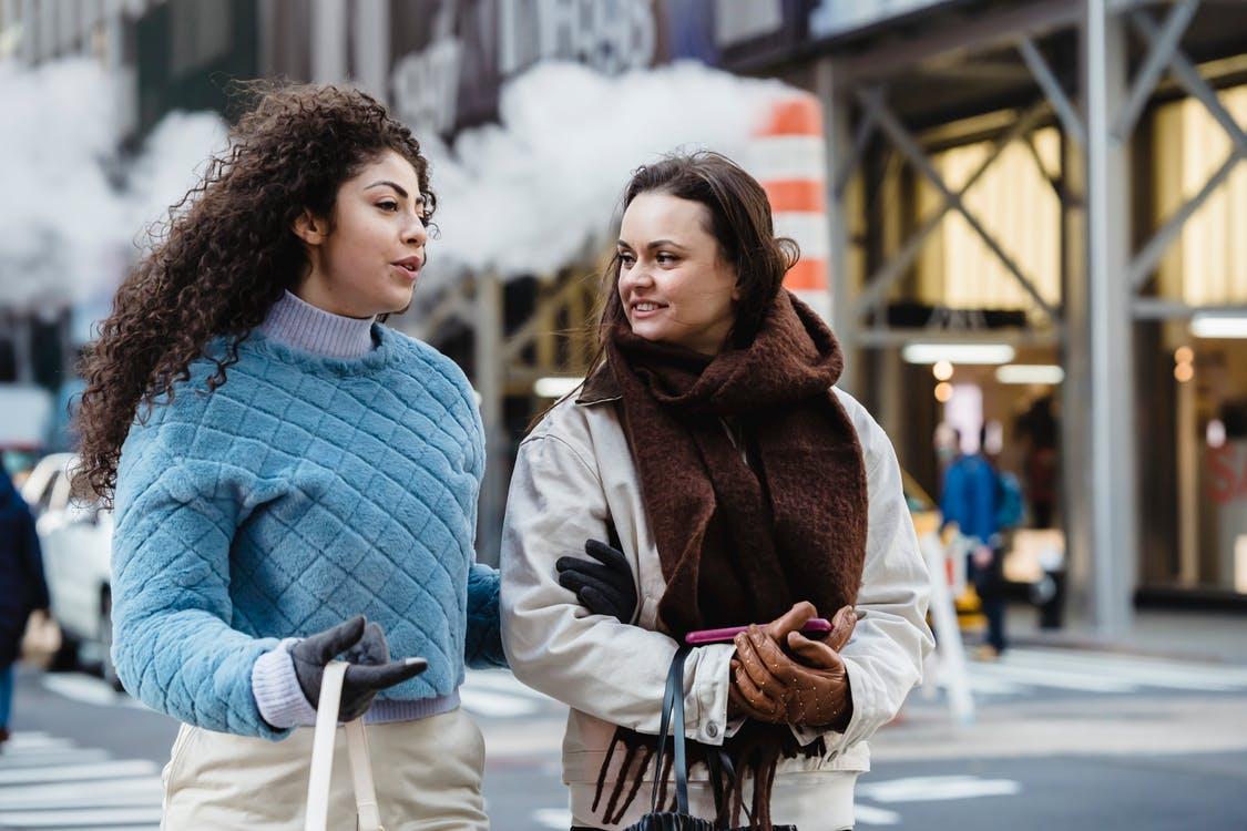 Positive stylish multiethnic women talking and crossing road in city