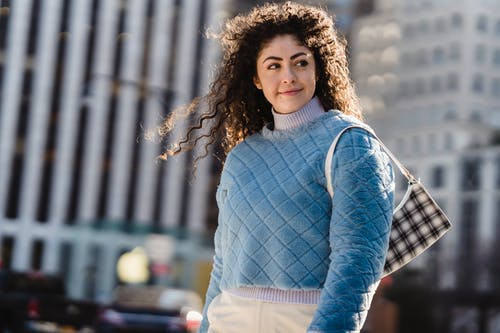 Positive young ethnic lady with long curly hair in stylish warm sweater smiling and looking away while standing on city street near modern skyscrapers on sunny day