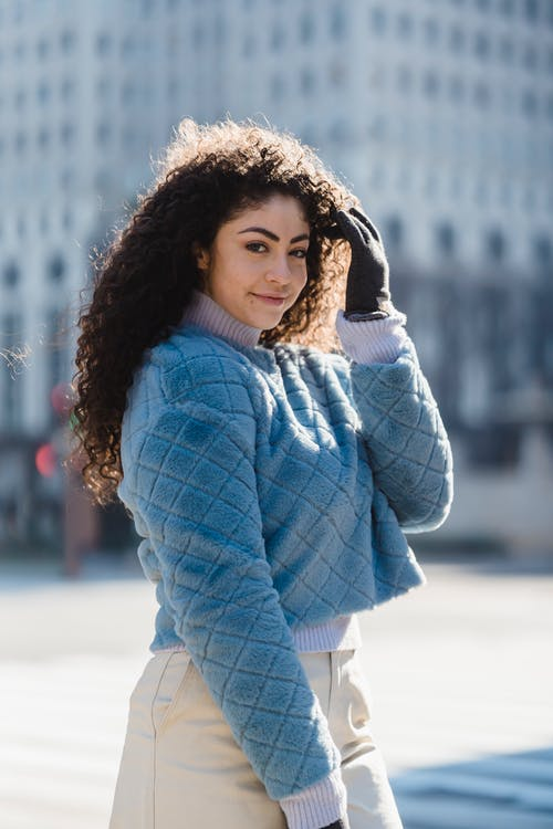 Cheerful young female in gloves and warm fashionable outfit smiling and looking at camera on blurred background of street