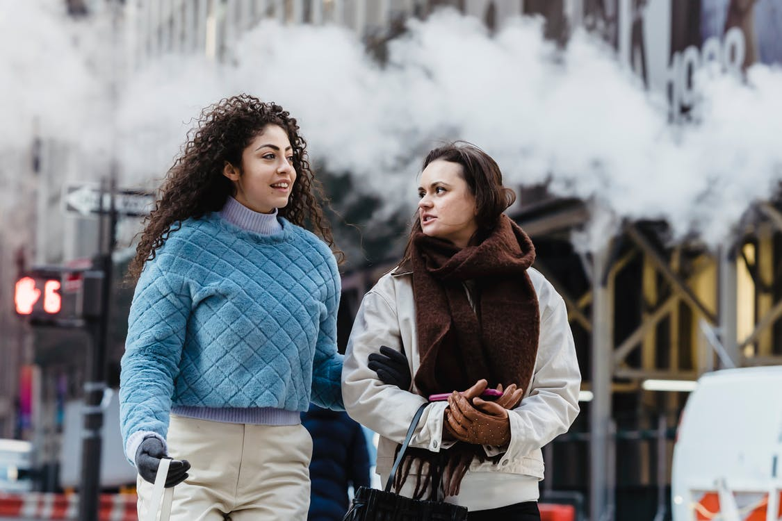 Young cheerful friends in trendy warm clothes chatting and walking