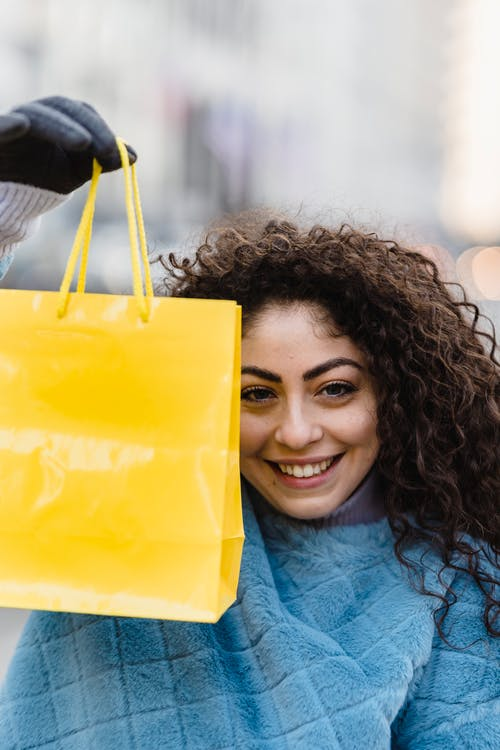 Cheerful woman with bright yellow gift bag
