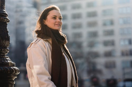 Glad female in trendy brown scarf smiling and looking away on blurred background of urban building