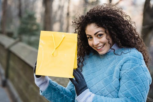 Young woman with bright yellow gift bag in hands
