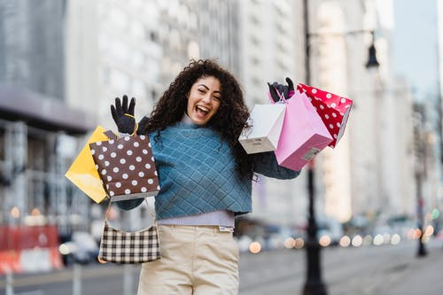 Positive woman with many different colorful gift bags