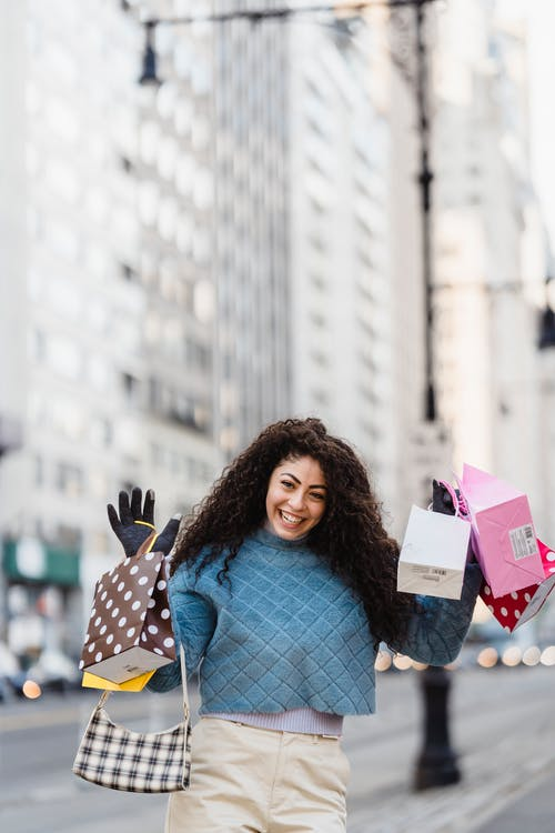 Positive young female in fashionable clothes demonstrating different gift bags on blurred background of modern street of city