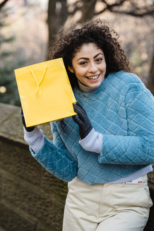 Cheerful woman with bright yellow gift bag after shopping