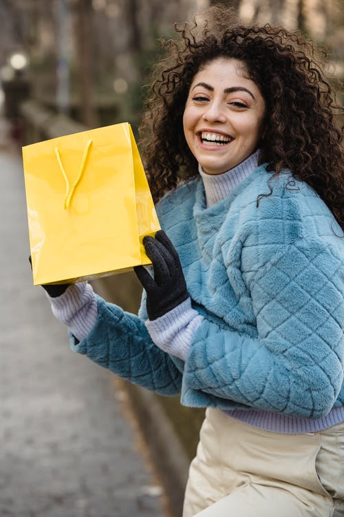 Young smiling woman showing yellow gift bag in park