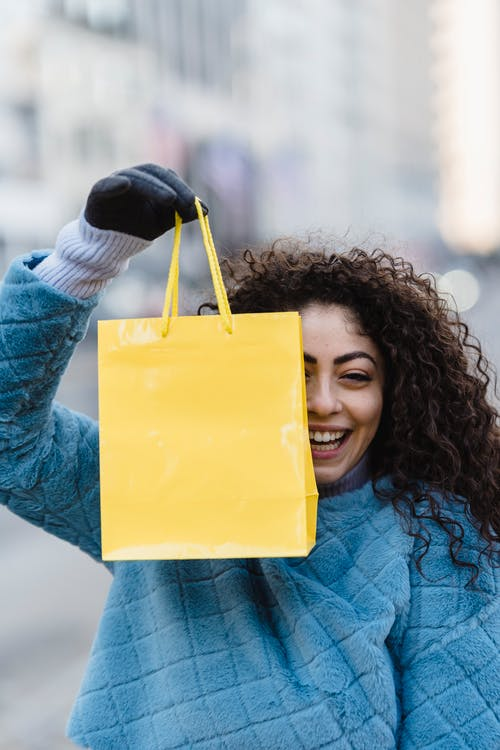Cheerful young female squinting and smiling while demonstrating yellow gift bag hanging in hand