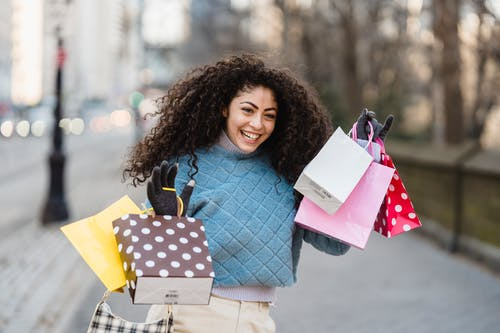 Cheerful shopper with bright gift bags smiling