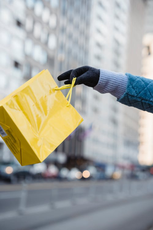 Woman showing ordinary yellow gift bag on street
