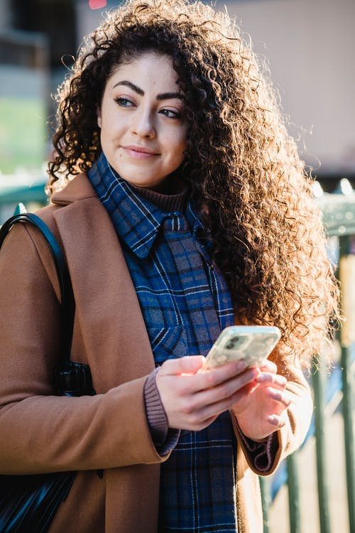 Young glad female with long curly hair texting message on mobile phone while looking away
