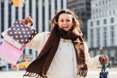 Happy young female carrying many bright gift bags while smiling and looking at camera on blurred background of street
