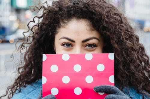 Woman with wrapped pink gift bag and curly hair