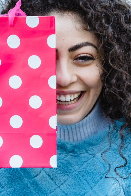 Young crop content cheerful female with bright pink gift bag smiling and looking at camera
