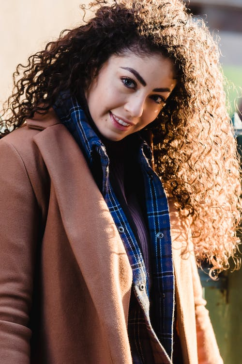 Content young happy woman with curly hair in trendy clothes
