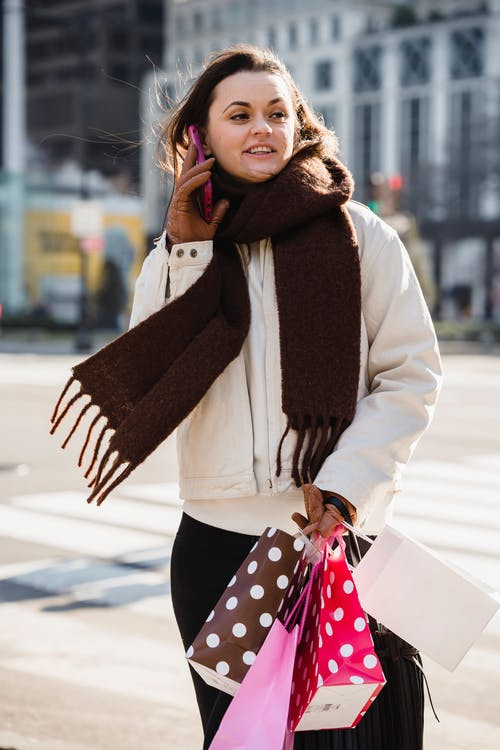Happy young female in brown scarf smiling and looking away while talking on mobile phone on blurred background of street