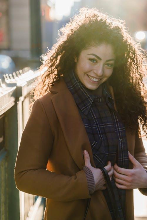 Happy young female with long hair in trendy clothes smiling and looking at camera in back lit