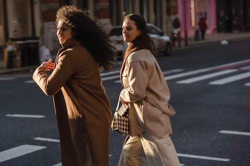 Stylish focused friends in fashionable coats walking across asphalt road with crosswalk in daytime