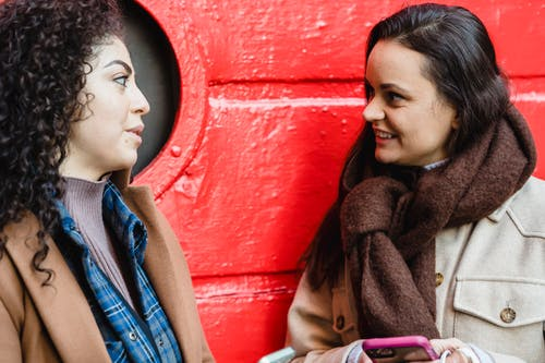 Young stylish ladies talking on street