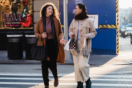 Joyful stylish multiethnic women crossing road and smiling