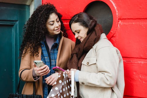 Positive young diverse female best friends in stylish warm clothes standing on city street near red door and browsing mobile phones