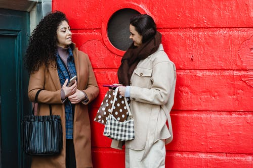 Positive young multiethnic ladies gossiping on street