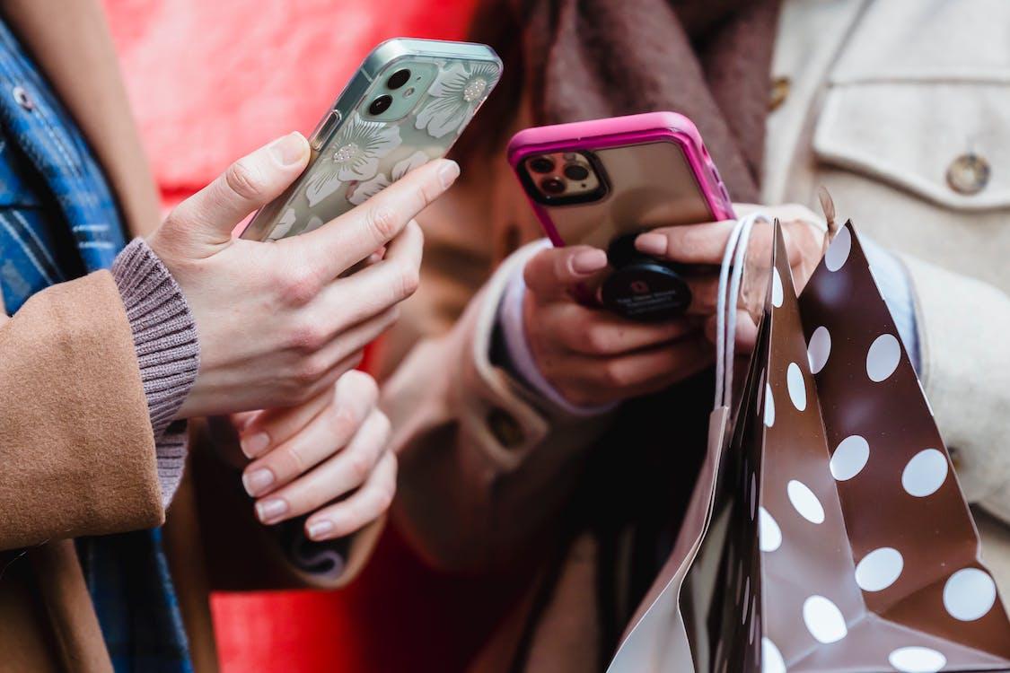 Unrecognizable ladies messaging smartphones on street