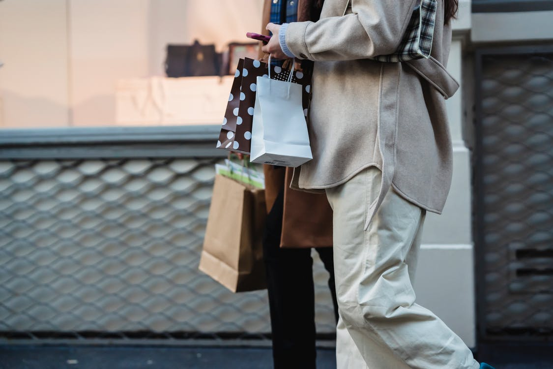 Side view of crop unrecognizable female shopaholics in trendy outfits with paper bags walking together on street after shopping and using smartphone