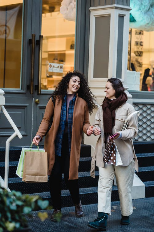 Full body of delighted young multiethnic ladies with dark hair in stylish outfits smiling and talking while walking on street near entrance of fashion boutique after shopping