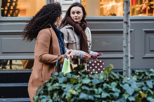 Side view of astonished young female friends in stylish warm outfits walking on street and looking at each other after shopping