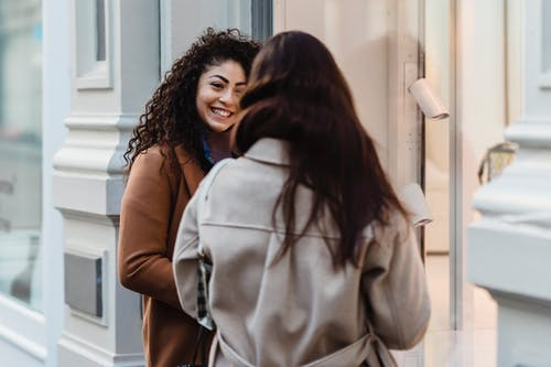 Happy young brunettes standing on street and talking
