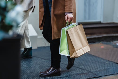 Anonymous woman strolling on street with shopping bags in daytime
