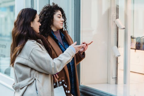 Side view of positive young multiracial female friends standing on city street and pointing on showcase of fashion boutique during shopping