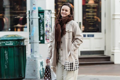 Positive young female in stylish warm clothes smiling while standing on city street near aged building with gift bags after successful shopping