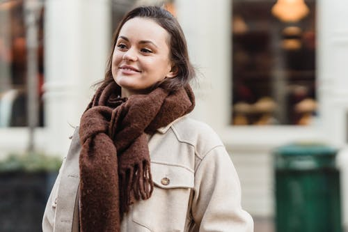 Confident young female with long brown hair in stylish coat and scarf smiling while standing on city street in daytime